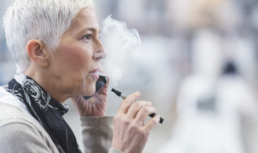 Woman on her mobile phone vaping/using an e-cigarette